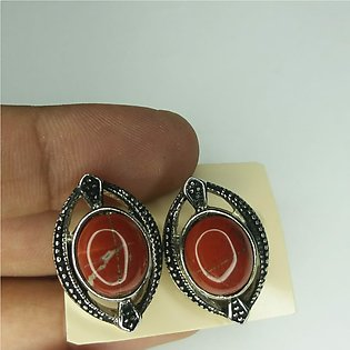 Black earrings with red solid stone in it